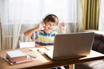 Boy performing online school work and making raise the roof gesture